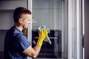 Mann, der eine Glasscheibe putzt in München