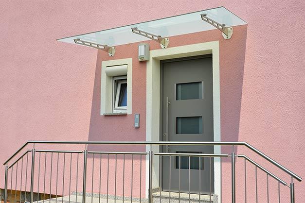 Moderner Hauseingangsbereich mit Glas Vordach an einem neu gebauten Haus